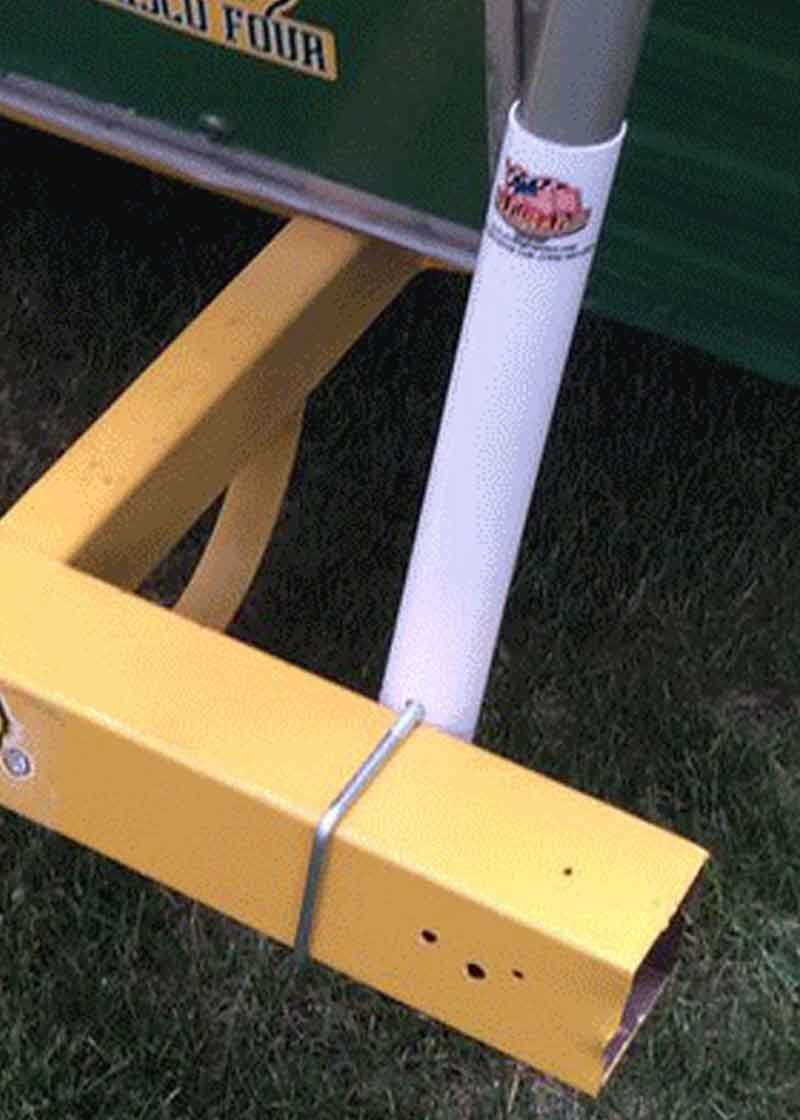 White flagpole bumper mount on a travel trailers back bumper to hold a flagpole. The bumper is yellow in color.