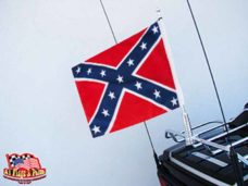 harley davidson motorcycle with 1 motorcycle flagpole with confederate flag mounted on the luggage rack.