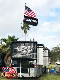 RV motorhome with a 22' flagpole and hitch flagpole mount. The flagpole is displaying the USA and NASCAR flags.